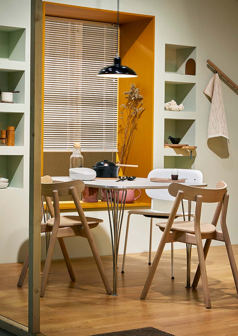 Dining room inspiration with pastel green and yellow wallpaint, round table and wooden chairs